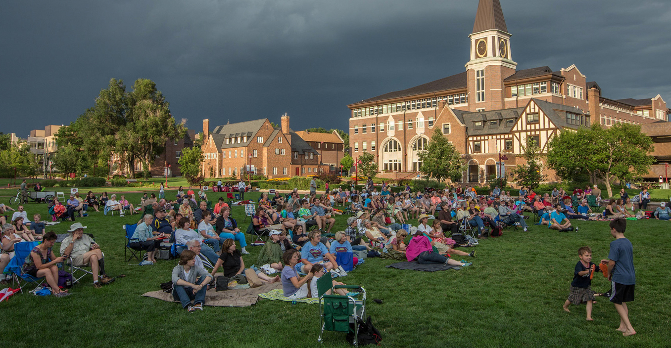 photo of community members sitting on campus grass