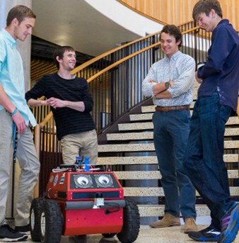 Students gather around a robot they built